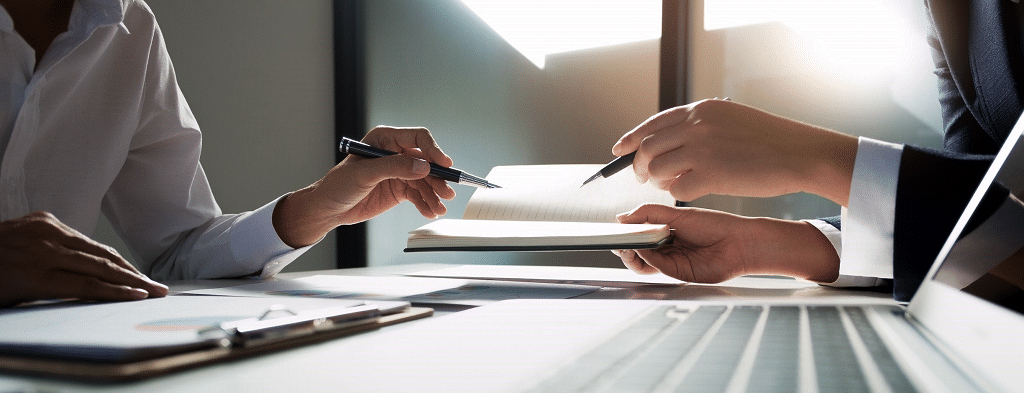 hands of two people negotiating over paperwork